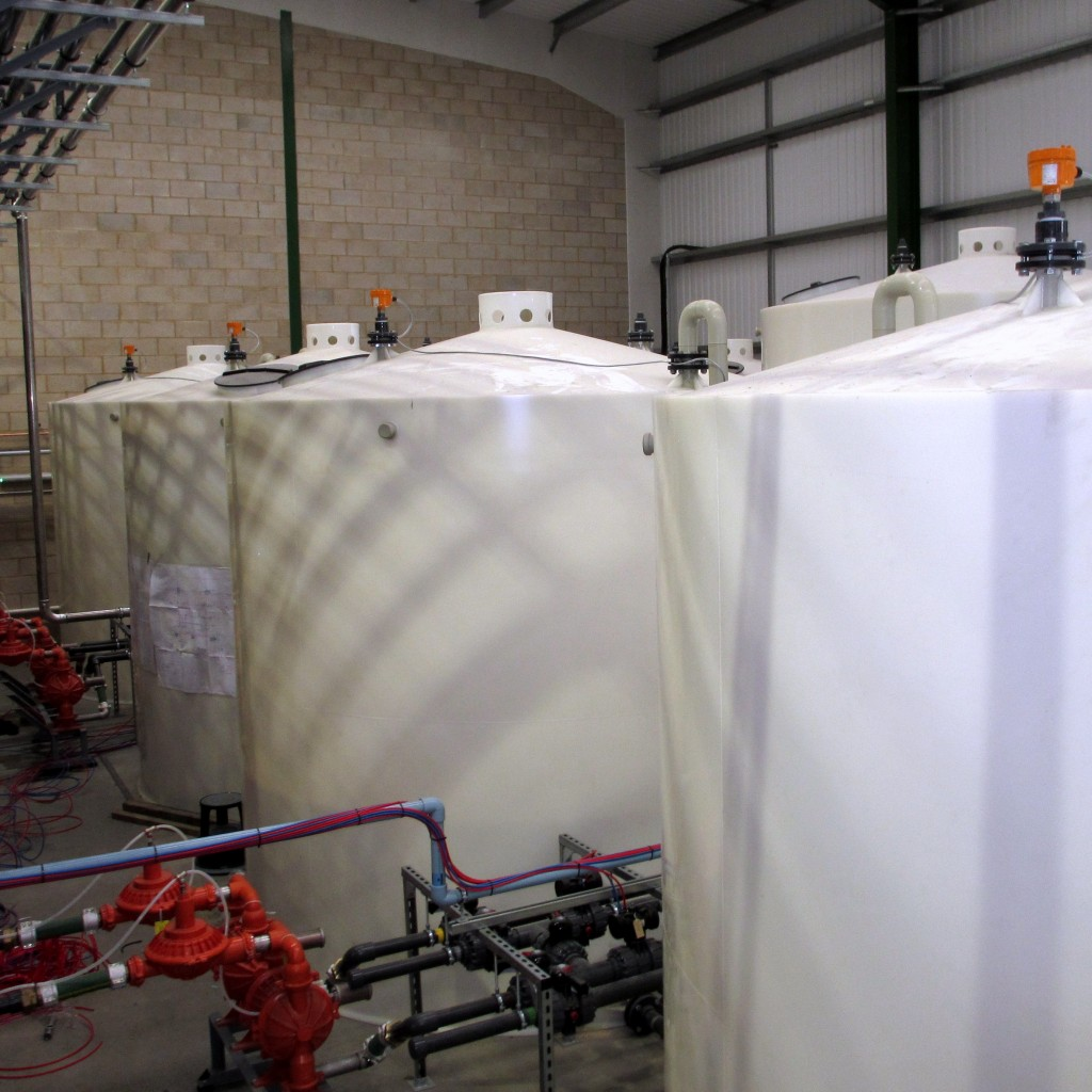 Series of Indoor Plastic Storage Tanks with Sloping Bases To Allow Maximum Drainage Out of Tank